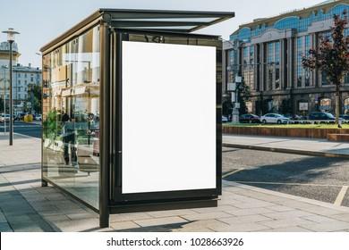 市内通りのバス停の白い垂直の掲示板。背景に建物と道路。モックアップ。車道の隣の通りのポスター。晴れた夏の日。