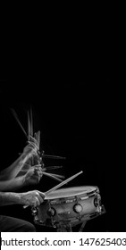 Vertical  B&W image of a stroboscopic drummer and sticks hitting a snare drum