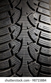 Vertical close up of a dirty snow tire with worn treads.
