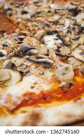 Vertical close up of freshly baked thin pizza with mushrooms, tomato sauce and mozzarella cheese