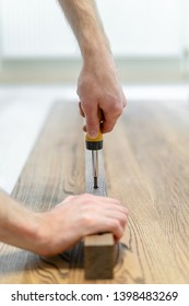 Vertical and close up photo of repairman holding in hand screwdriver tool and making repair or assemble new wooden desk or table top