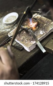 Vertical close up shot of Jeweler crafting golden bracelet with flame torch.