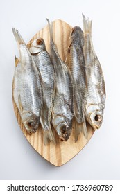 vertical close up top view shot of a bunch of five Russian dried salted vobla (Caspian Roach) fish on a wooden plate on a white background