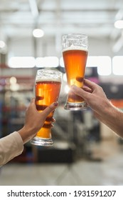 Vertical close up of two workers holding beer glasses while inspecting quality of production and filtration at brewery, copy space