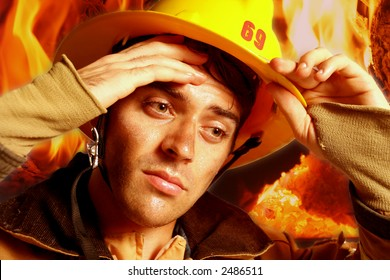Vertical close-up of a firefighter in his gear wiping sweat from forehead with fire in background