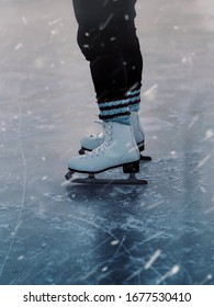 A vertical closeup of a person in white skates on the ice during the snowfall