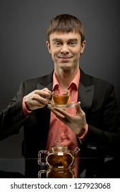 vertical closeup portrait  the  beautiful man hold cup with green  tea,  on brown background