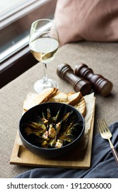 A vertical closeup shot of gourmet cooked oysters and clams with a glass of whitewine