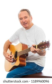 Vertical close-up shot of a mature man happily playing his guitar on a white background.  Copy space.