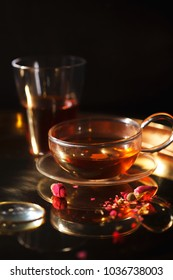 Vertical close-up shot of small glass teapot and cup with hot red tea, dried rose petals, pocket magnifier on golden chain on golden tray. Evening light. Golden color concept.