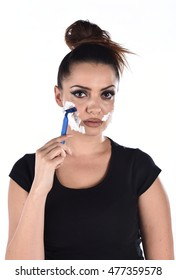 vertical closeup studio portrait on a white background of a beautiful young brunette woman wearing black shirt with shaving cream on her face and holding a razor on her cheek