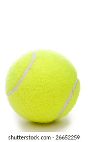 A vertical closeup of a yellow tennis ball on a white background