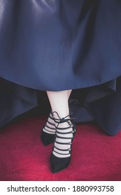 A vertical closup shot of black ballet shoes on a dancer's fe