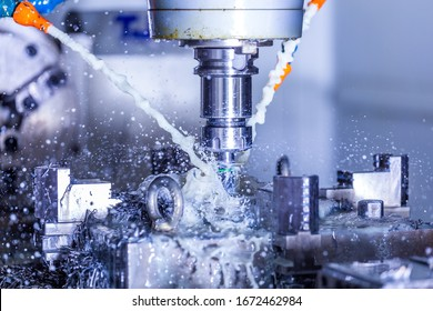 vertical cnc steel milling process with external water coolant streams, splashes and a lot of metal chips, high contrast