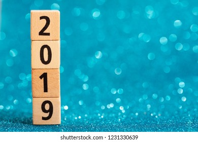 Vertical column of numbers 2019 on blue sparkling background. Place for text. Festive concept.