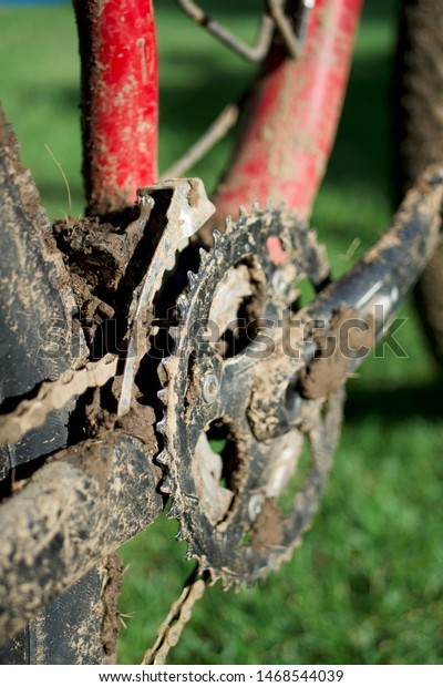 Vertical composition, close-up of muddy crankset on red mountain bike after a ride.
