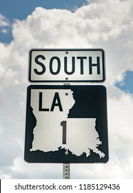 A vertical composition of a Louisiana highway 1 south roadside sign post