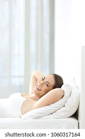Vertical composition of a relaxed woman looking at camera on the bed at home