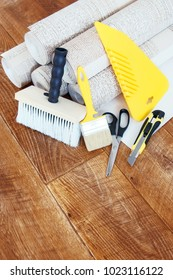 Vertical composition with some tools for wallpapering and rolls of wallpaper on wooden floor