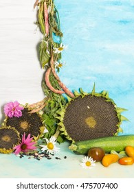 vertical country ripe autumn still life with sunflowers, beans, tomatomi, zucchini and garden flowers on a background of blue and white painted wall