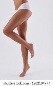 Vertical cropped portrait of young lady in white panties demonstrating slender legs