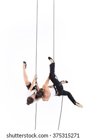 Vertical dance. Two women dressed executive with harnesses hanging from a climbing rope doing stunts