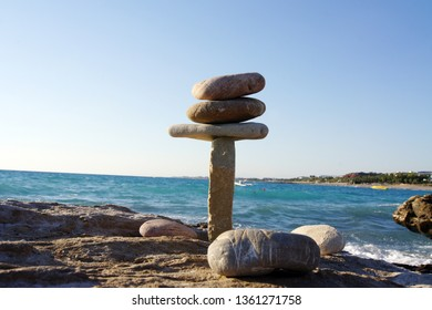 Vertical design of balancing stones, shot close-up on the beach in Turkey, against the blue sea and sky