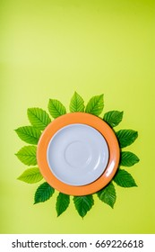 Vertical design of an white empty plate over orange one surrounded by leaves on green background