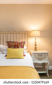 Vertical detail shot of a contemporary bedroom with white linen, yellow blanket and pillow, bedside table with classic lamp shade, wooden headboard and beige wall.