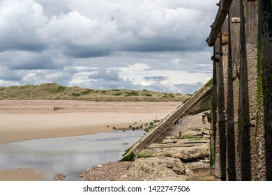 Vertical and diagonal wooden sea defences hold back waters of the fast-flowing River Arun, Littlehampton, West Sussex, UK protecting a sandy beach and grass covered dunes. The sky is overcast cloudy.