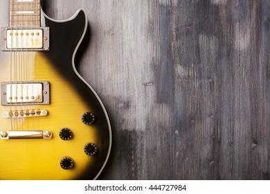 Vertical electric sunburst guitar on dark wooden surface. Closeup, Mock up