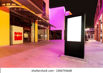 Vertical empty billboard placeholder template on the street at night, side view