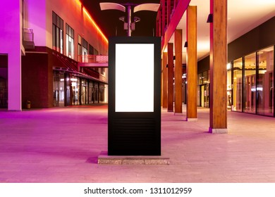 Vertical empty billboard placeholder template on the street at night, front view