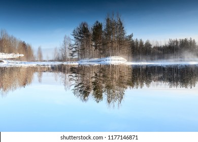 Vertical flip picture of reflection from lake shore in water surface, winter season with unfrozen lake at sunny frost day