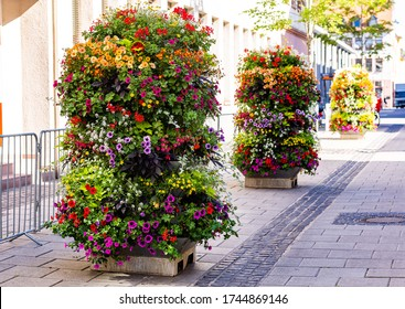 Vertical flowerbeds in the city. Flowers on the street. Urban decoration. Summer in city. Well-kept streets. Pleasant surroundings. Flower beds full of flowers.