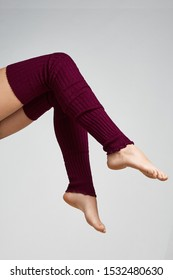 The vertical format shot of female legs in maroon ribbed gaiters above the knee. The fashion model bent two knees.The photo is made in the studio on the light-gray background