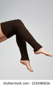 The vertical format shot of female legs in khaki ribbed gaiters above the knee. The fashion model bent two knees. The photo is made in the studio on the light-gray background