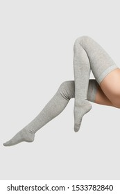 The vertical format shot of female legs in gray self-coloured shadow-proof stockings over knee socks out pattern. The fashion model bent two knees. The photo was taken on a white background.