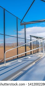 Vertical frame Sunlit bleachers overlooking a vast sports field on the other side of the fence
