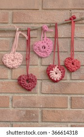 a vertical frontal view of some hearts hanging on a branch over a brick background with space for a message