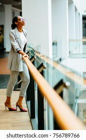 Vertical full height of elegant african woman in glasses and gray suit standing at railing in business center or shopping mall. Side view. Looking up. Lifestyle, leisure and people concept.