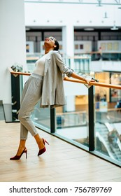Vertical full height of elegant fashionable african woman in glasses and gray suit holding at railing in business center or shopping mall. Looking up. Lifestyle, leisure and people concept.