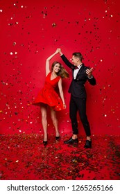 Vertical full length body size view of two nice graceful exquisite attractive cheerful spouses rejoicing decorative elements having fun christmas festive isolated on bright vivid shine red background