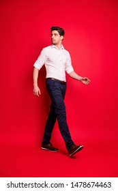 Vertical full length body size photo of turned serious confident man looking back while isolated with red background