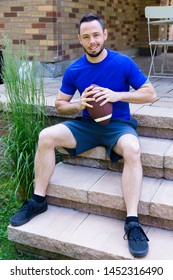 Vertical full length frontal view of handsome clean cut smiling young man in sports clothes sitting waiting on terrace holding small American football ball