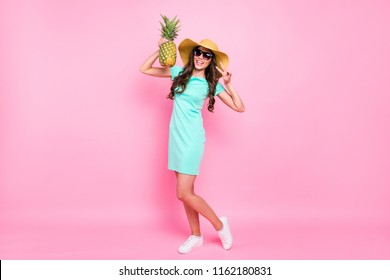 Vertical full length, legs, body, size portrait of young woman holding a pineapple and showing v-sign standing in a turquoise mini dress and white sneakers isolated on vivid pink background