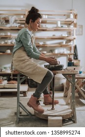 Vertical full length portrait of charming craftswoman kneading and shaping clay in pottery workshop
