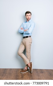 Vertical full length portrait of half turned, confident, handsome, stunning man with crossed hands standing near grey wall on wooden floor looking to the side