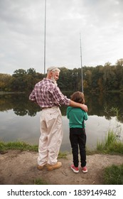Vertical full length rear view shot of a senior fisherman hugging his grandson while fishing together on the lake