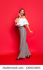 Vertical full size body length profile side view portrait of fascinating lovely attractive lady wearing white off-the-shoulders top striped pants touching cheek going isolated over red background